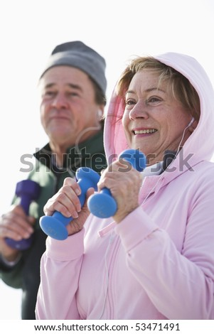 Close up of mature couple exercising with hand weights - stock photo