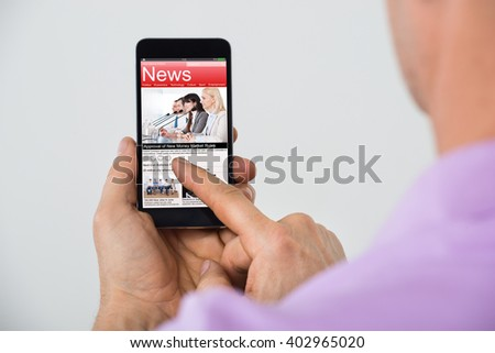 Close-up Of Mature Man Reading News On Smartphone - stock photo