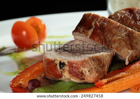 Close-up of meat with vegetables garnish on a white plate on a black background studio