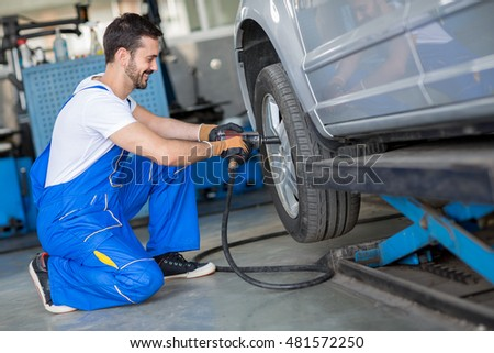 Close up of mechanic changing wheel on car with pneumatic wrench