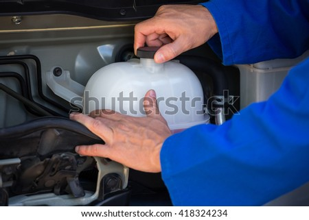 Close-up of mechanic checking a coolant water tank at the repair garage - stock photo