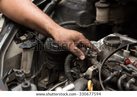 Close up of mechanic hand fix the engine - stock photo
