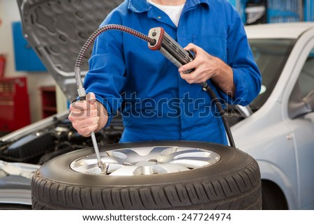 Close up of mechanic inflating the tire at the repair garage - stock photo