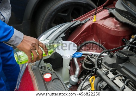 Close-up Of Mechanic Pouring Oil Into The Car Engine