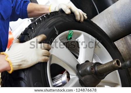 Close-up of mechanic repairman hands during balancing automobile car wheel on balancer - stock photo