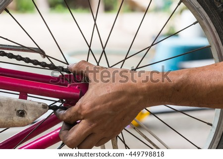 close-up of mechanic setting up chain on bicycle in workshop - stock photo