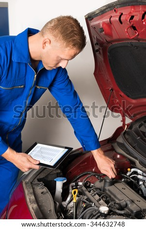 Close-up Of Mechanic Using Digital Tablet While Examining Car Engine In Garage - stock photo