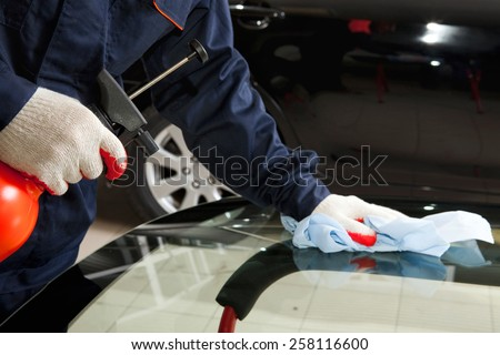 Close-up of mechanic working in Auto Repair Shop: cleaning the new car windshield - stock photo
