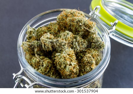 Close up of medical marijuana buds in glass container on black background - stock photo