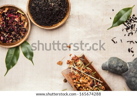 Close-up of medicinal and aromatic plants, leaves and an Asian ancient statue, symbol of traditional Chinese medicine - stock photo