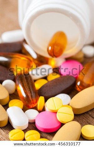 Close up of medicine tablets and white plastic bottle on a wooden background