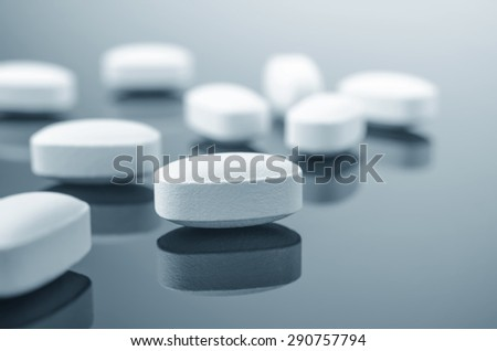 Close-up of medicine tablets on reflective surface - stock photo