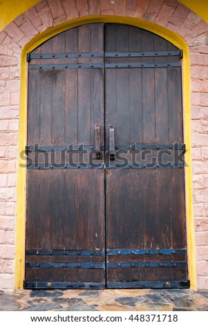 Close-up of medieval wood entrance doorway with ancient brick arc doorway