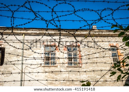 Close-up of metal barbed wire fence against of Patarei prison of Tallinn, Estonia - stock photo