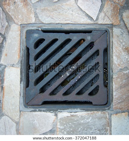 close up of metal grate drain on walkway - stock photo