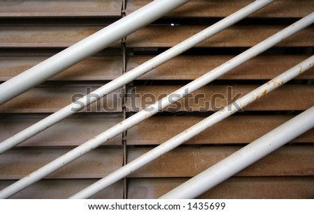 close up of metal handrail and rusting metal shutters