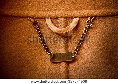 Close-up of metal hanging chain with blank tag inside brown wool coat. - stock photo