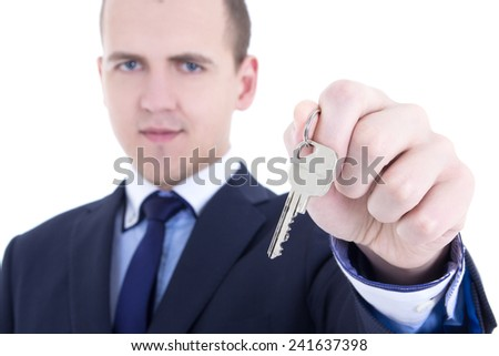 close up of metal key in male real estate agent hand isolated on white background
