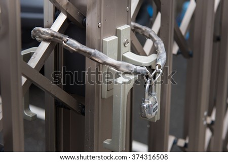 Close up of metal lock with chain hang on slide door - stock photo
