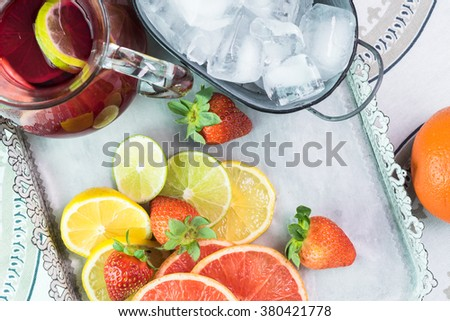 Close up of metal tray with pitcher of sangria, bucket of ice and slices of fruits and strawberries.