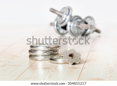 Close up of metallic extra weight plates on wooden floor and dumbbells in background