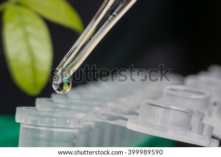 Close-up of micro centrifuge tube in front of green leaf on black background - stock photo