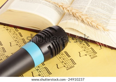 Close up of microphone and bible on a yellow music sheet - stock photo