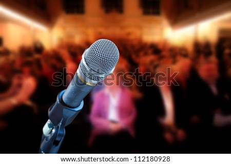 Close up of microphone in concert hall, with audience in background - stock photo