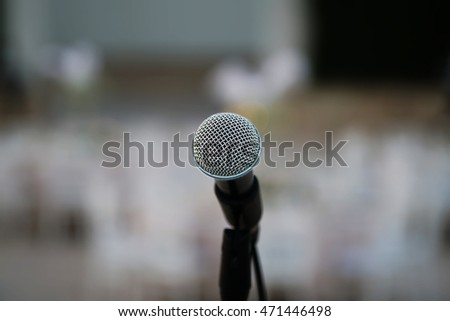 Close up of microphone in concert hall, with audience in background