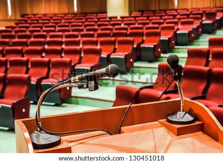 Close up of microphone in conference hall - stock photo