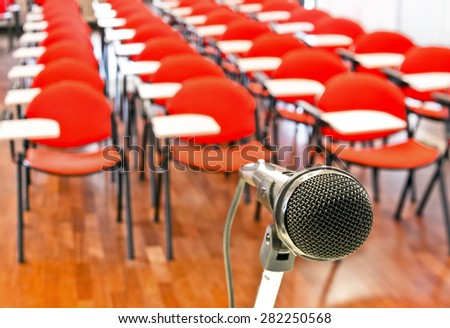 Close up of microphone in front of empty chairs in conference room - stock photo
