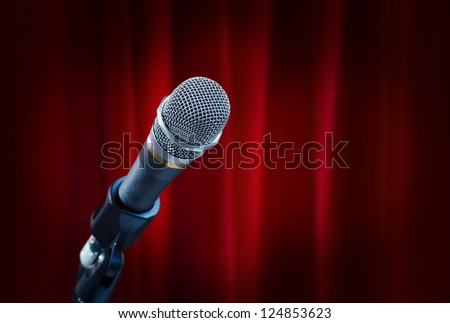 Close up of microphone in front of red curtain