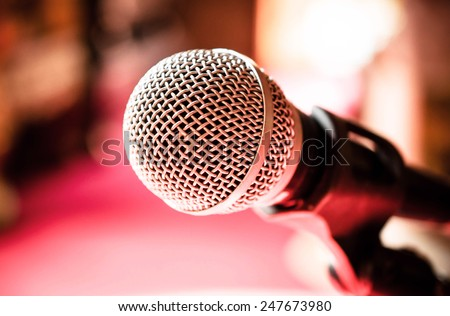 Close up of microphone in karaoke room or conference room / Microphone in karaoke room or conference room/ Close up of microphone in front of pink background (microphone, karaoke, music ) - stock photo