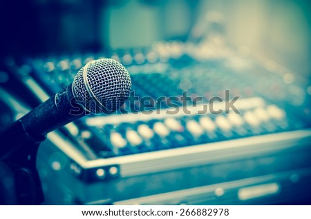 Close up of microphone on mixer blurred background - stock photo