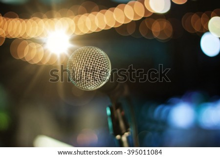 Close up of microphone on stage at outdoor night party, abstract bokeh light background