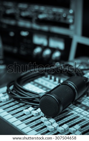 Close up of microphone with equipment on mixer in music studio, music instrument concept - stock photo