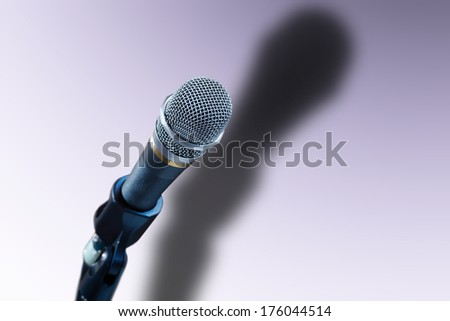 Close up of microphone with shadow in purple light