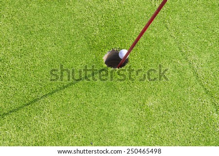 Close-up of mini golf ball going in the  hole - stock photo