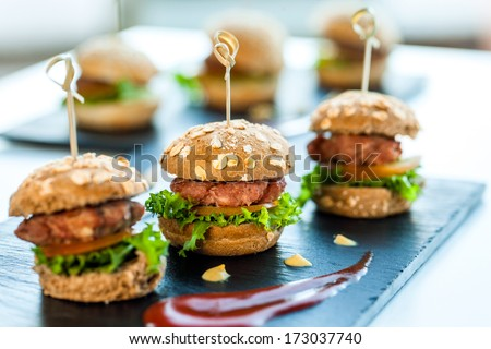 Close up of mini hamburgers at catering event. - stock photo
