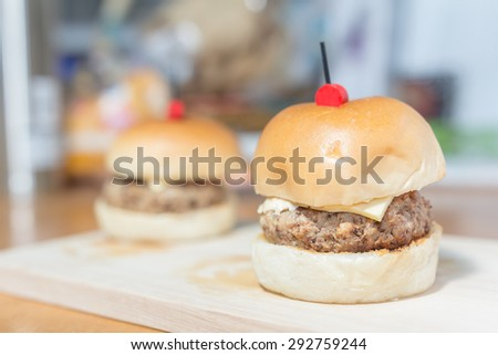 Close-up of mini hamburgers on a wooden board - stock photo