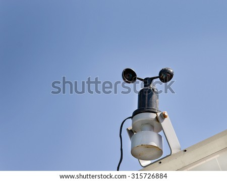 Close up of mini weather station against blue sky - stock photo