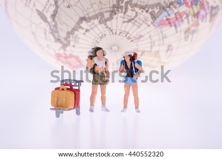 Close up of Miniature backpacker and tourist people with earth in background for travel concept - stock photo