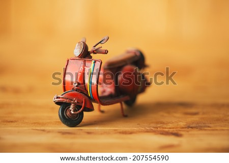 Close-up of miniature hand made toy motorcycle on rustic wooden background - stock photo