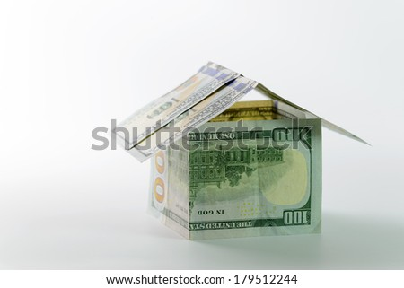 Close up of miniature house build with US dollar - stock photo