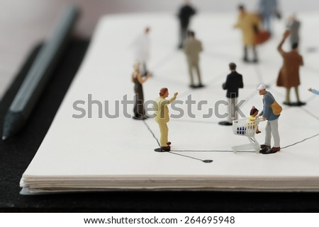 close up of miniature people with social network diagram on open notebook on wooden desk as social media concept - stock photo