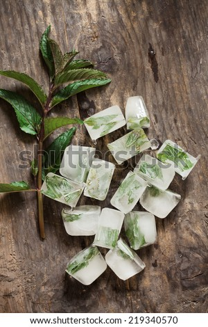 Close-up of mint ice cubes on a wooden table. - stock photo