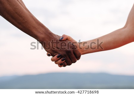 Close-up of mixed race couple holding hands on the misty mountain background. Symbolic photo
