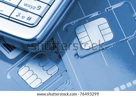 Close-up of mobile phone with sim cards. Toned in blue - stock photo