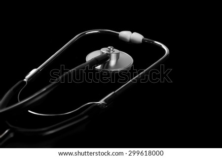Close-up Of Modern Acoustic Stethoscope Isolated On Black Background In Dark Light With Copy Space - stock photo