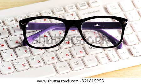 close up of  modern glasses on white computer keyboard
